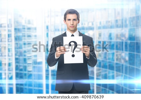 Portrait of business man handing question mark, blue background. Concept of problem and solution - stock photo