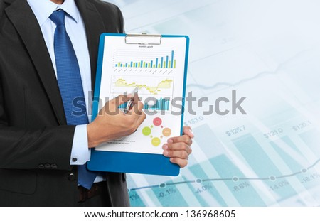 portrait of business man holding a report. growth chart concept - stock photo