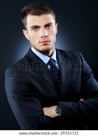 Portrait of business man isolated on dark background - stock photo