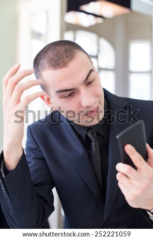 Portrait of business man looking at his smartphone in confusion - stock photo