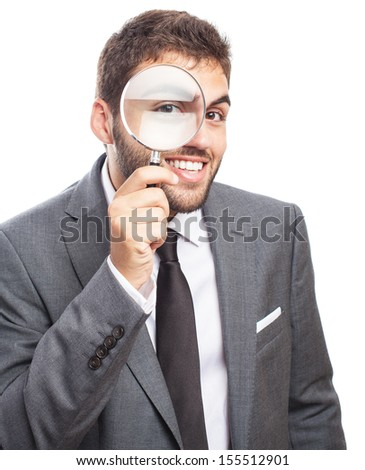 portrait of business man looking through a magnifying glass on white - stock photo