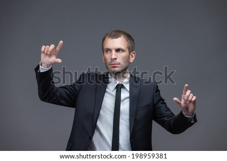 Portrait of business man pointing finger gestures, isolated on white on grey background. Concept of leadership and success