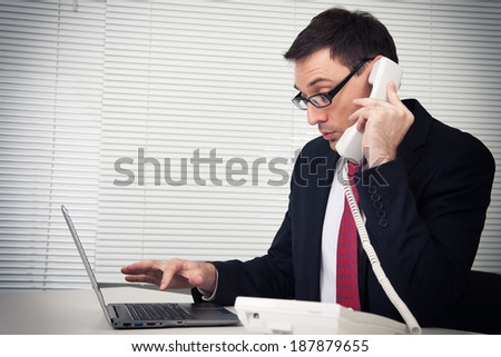 Portrait of business man speaking on phone, sitting at desk, looking at laptop - stock photo