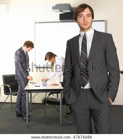 Portrait of business man with team mates discussing in the background