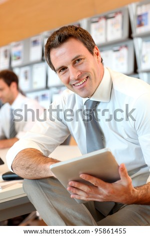 Portrait of business manager using electronic tablet - stock photo