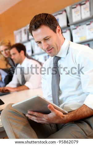 Portrait of business manager using electronic tablet