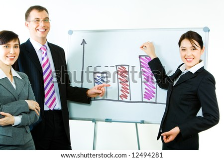 Portrait of business partners standing near whiteboard with graphs on it and pointing at the chart looking at camera with smiles - stock photo