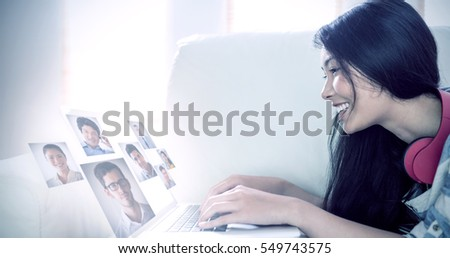 Portrait of business people against smiling asian woman on couch using laptop