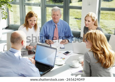 Portrait of business people discussing in a meeting while sitting at conference desk and using laptop and digital tablet. - stock photo