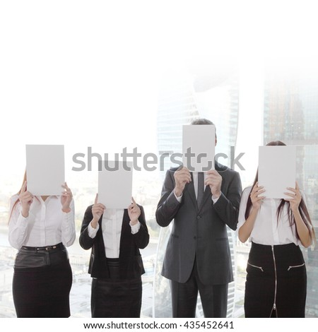 Portrait of business people group holding white papers and covering their faces