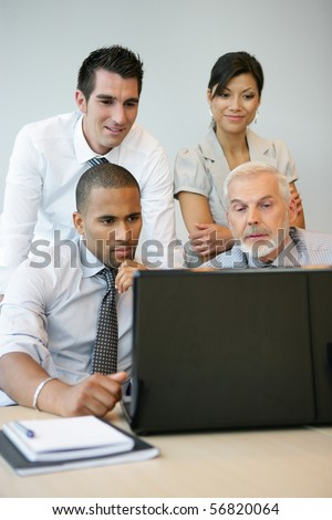 Portrait of business people in a meeting with a laptop computer - stock photo