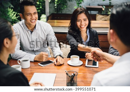 portrait of Business people shaking hands, finishing up a meeting