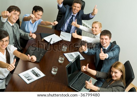 Portrait of business people showing thumbs up and looking at camera - stock photo
