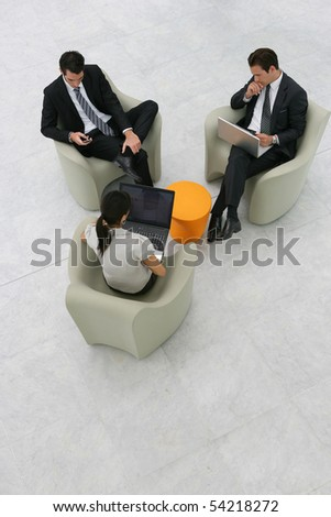 Portrait of business people sitting on armchairs with laptop computers and a phone - stock photo