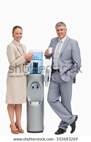 Portrait of business people smiling next to the water dispenser against white background - stock photo