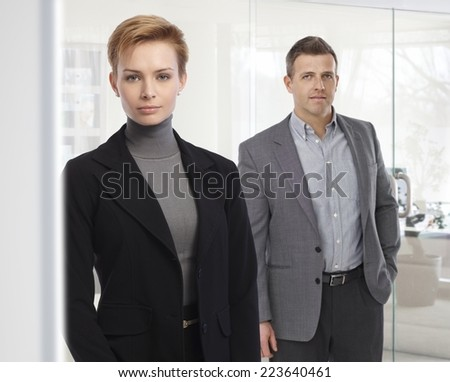 Portrait of business people standing at office, wearing suit, looking at camera, bright background. Attractive, confident caucasian woman. - stock photo
