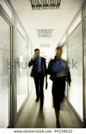 Portrait of business people walking down long corridor in office building - stock photo