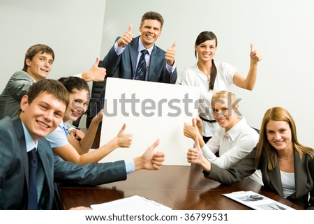 Portrait of business people with thumbs up holding blank cardboard and smiling at camera - stock photo