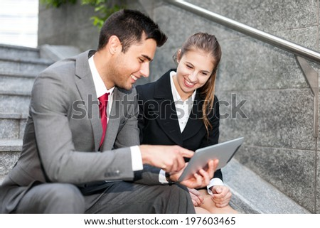 Portrait of business people working on a digital tablet
