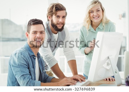 Portrait of business professionals discussing at computer desk in office - stock photo