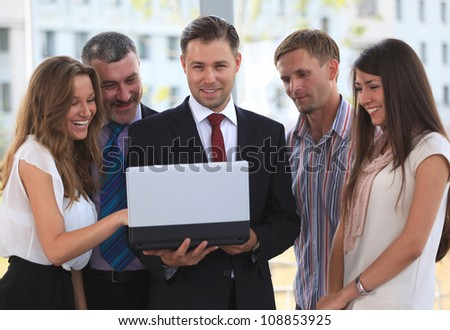 Portrait of  business team discussing while looking at laptop together - stock photo