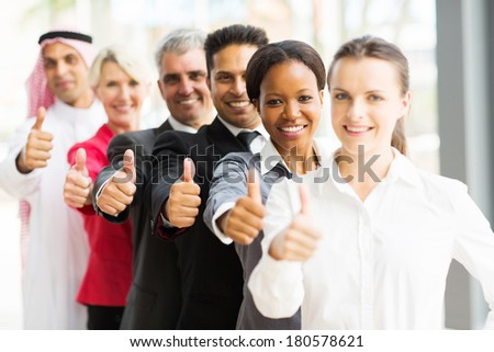 portrait of business team in a row giving thumbs up - stock photo