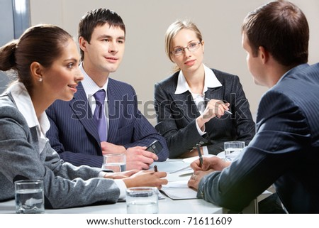 Portrait of business team interviewing man - stock photo
