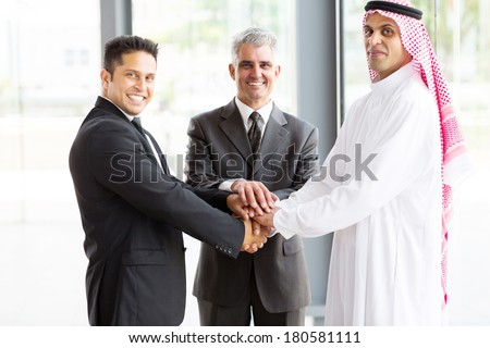 portrait of business team putting their hands on top of each other - stock photo