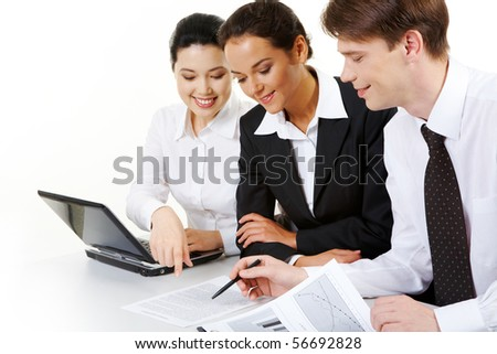 Portrait of business team sitting around table and looking at document while confident man pointing at it