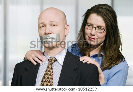 Portrait of Business team - the man is being muzzled with duct tape - stock photo