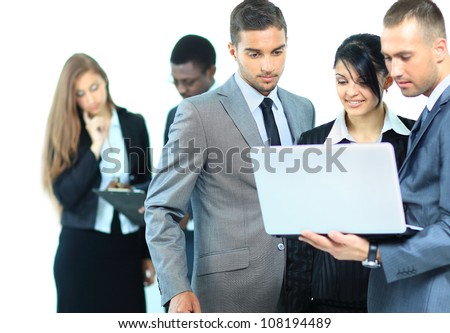 Portrait of business team working on laptop together