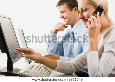 Portrait of business woman calling on the phone pointing to the monitor on a background of her colleague - stock photo