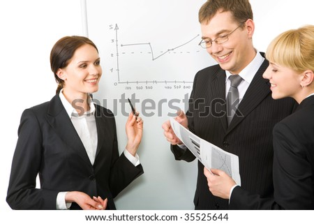 Portrait of business woman explaining her ideas to partners on the whiteboard at seminar - stock photo