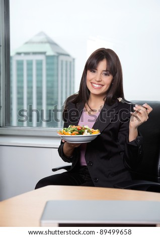 Portrait of business woman having fresh salad of vegetables - stock photo