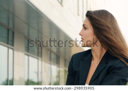 Portrait of business woman in a dark suit against the office building