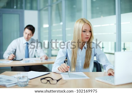 Portrait of business woman looking at laptop screen in office - stock photo
