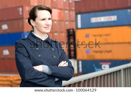 Portrait of business woman looking away in front of container terminal - stock photo