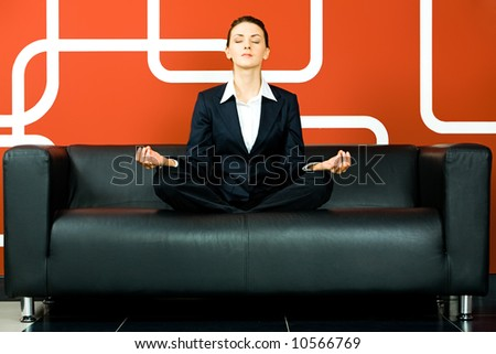 Portrait of business woman meditating on the sofa in the room - stock photo