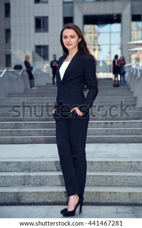Portrait of business woman on the background of people, and office building.
