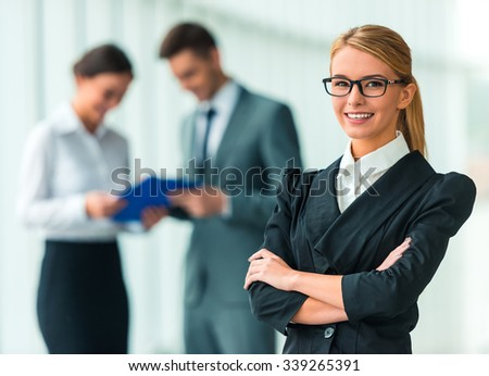 Portrait of business woman on the background of their colleagues in the office - stock photo