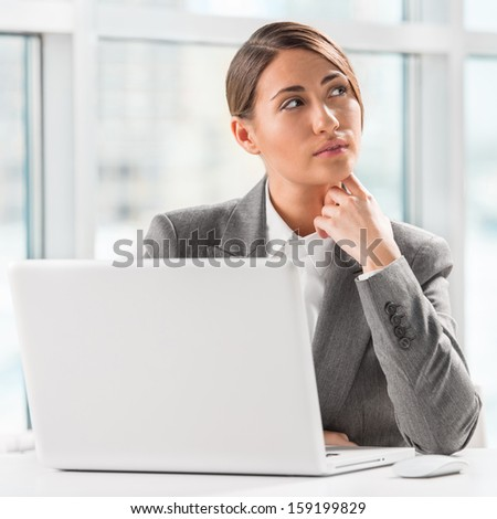 Portrait of business woman resting chin on hand in front of her laptop at office - stock photo
