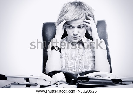 Portrait of business woman sitting at a desk in the office with many telephone with sad face, toned image