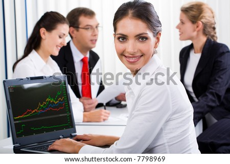 Portrait of business woman sitting at the desk in the office - stock photo