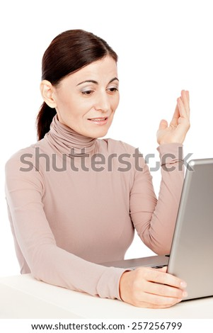 Portrait of  business woman sitting in front of laptop computer looking at screen, communicating by web. Isolated white background.  - stock photo