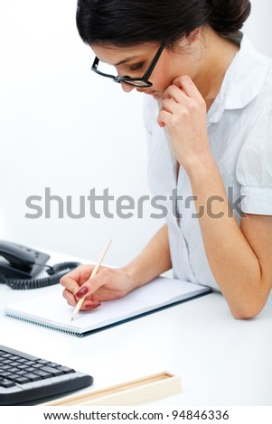 Portrait of  business woman taking note in a notepad at office