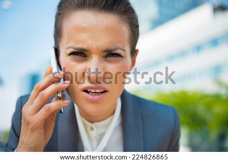 Portrait of business woman talking cell phone in office district