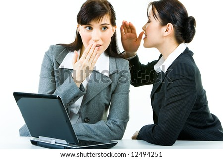 Portrait of business woman telling a secret to another one while at work - stock photo