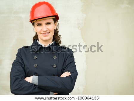 Portrait of business woman wearing protection helm against the new building wall - stock photo