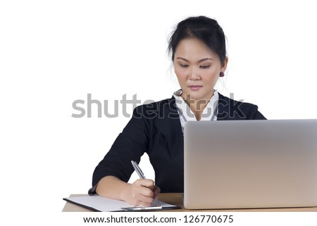 Portrait of business woman with laptop writes on a document at her office, Isolated on white background. Model is Asian woman. - stock photo