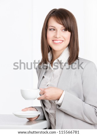 Portrait of business woman with white cup and saucer, isolated on white - stock photo